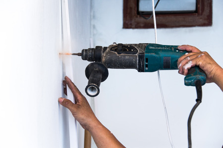 close up of electric drill making hole in a wall: repair, building and home concept