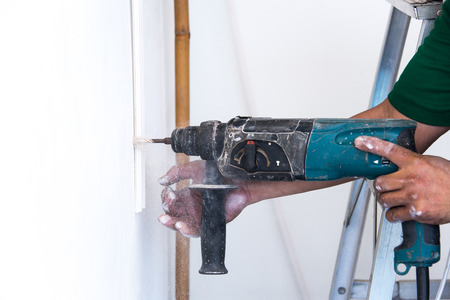 making hole: close up of electric drill making hole in a wall: repair, building and home concept
