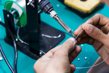 worker is soldering cable