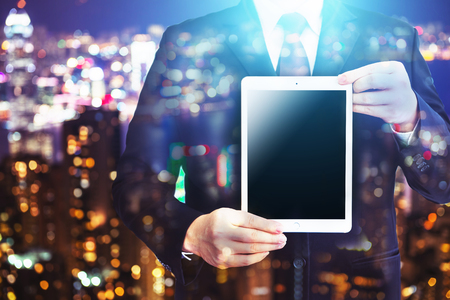 Business man holding tablet on blurry background.