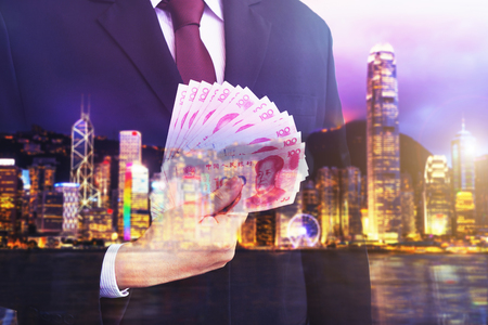 Business man holding Chinese money (RMB) on blurry background.