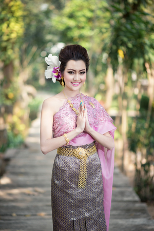 Beautiful Thai girl in Thai traditional costume in Thais greeting gesture