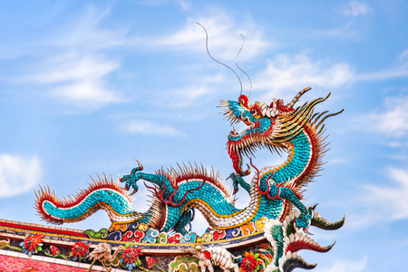 Beautiful dragon crawling on the decorative tile roof in Chinese temples. Colorful roof detail of traditional Chinese temple