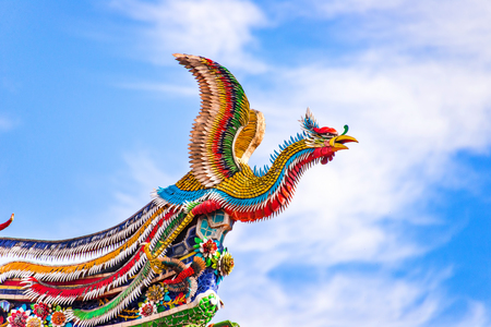 Beautiful Phoenix flying on the decorative tile roof in Chinese temples. Colorful roof detail of traditional Chinese temple Stock fotó