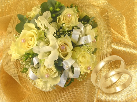 wedding bouquet with gold wedding rings on golden background photo