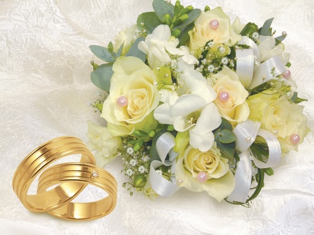 engagement party: wedding bouquet with gold wedding rings on white background