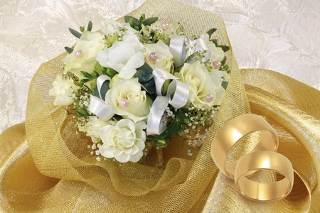 rose ring: wedding bouquet with gold wedding rings on white background