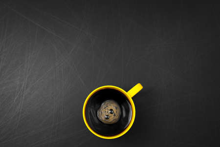 Clockwise stir. Yellow cup of black coffee flat lay on scratched rough black background. Copy space for your text, image or message. Minimal, top view, horizontal image style. Off-center composition.