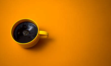 Yellow mug of stirring black coffee flat lay on dark yellow color background. Copy space for your text, image or message. Minimal, top view, horizontal image style. Off-center composition.