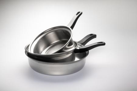 utensilios de cocina: Ollas de acero inoxidable limpio y brillante y cacerolas de acero. Foto de archivo