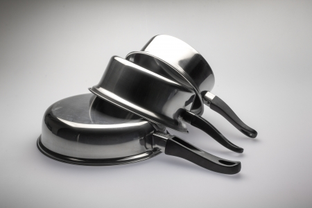 cooking ware: Clean and shiny stainless steel pots and pans.