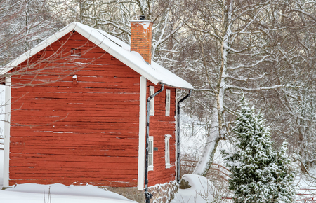 a red house with snow on the roof and forest in the background