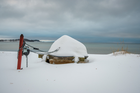 Snow covered boat upside down on the beach and the sea in the background Standard-Bild - 122721910