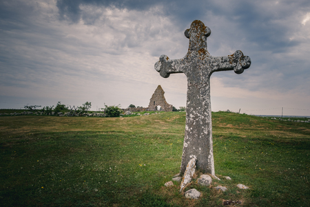 old cross in stone and ruins in the background