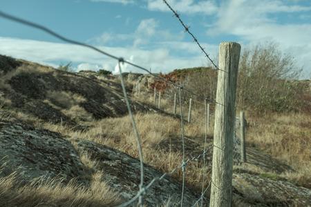 fence with wooden poles and nets on rocks Reklamní fotografie