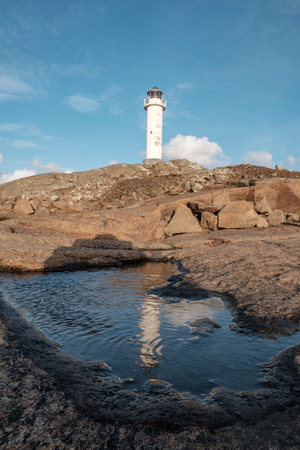 white lighthouse with reflections in the puddle in the foreground Imagens