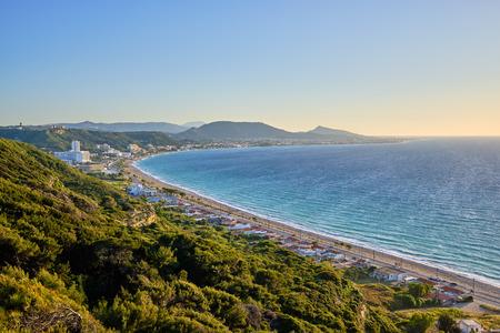schöner Blick auf das Meer mit Resort und Bergen im Hintergrund und grünen Büschen im Vordergrund