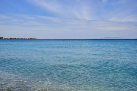 calm sea of turquoise color and some clouds in the blue sky