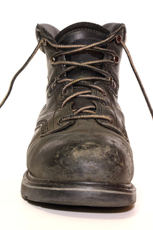 Scuffed work boot isolated in front of a white, seamless background