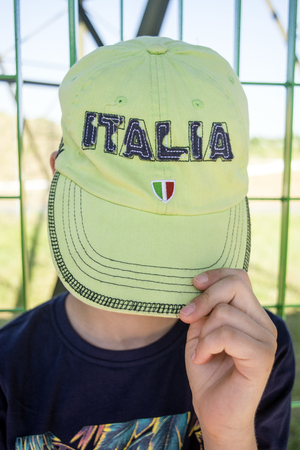 A boy hiding his face with a hat on with the word ITALIA written and the colors of the Italian flag