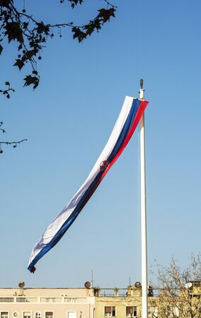 A flag flies at mast in front of Serbian parliament