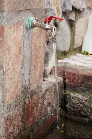 Faucet in a brick wall and running water Foto de archivo