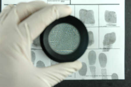 comparing the fingerprint through the dactyloscopic magnifier glass Stock Photo - 6057368