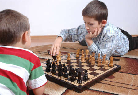 Two young boys playing chess photo