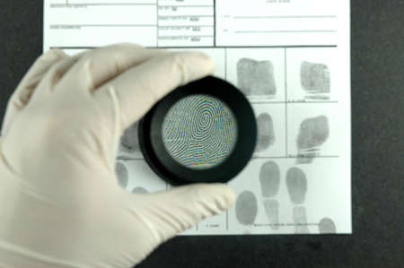comparing the fingerprint through the dactyloscopic magnifier glass Stock Photo - 6270246