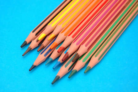 striped coloured pencils on blue background Stock Photo - 6343874