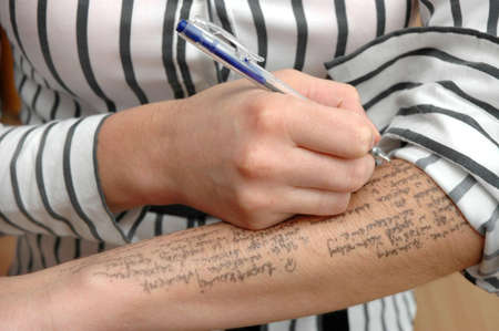 Student writes information on hand on exam
