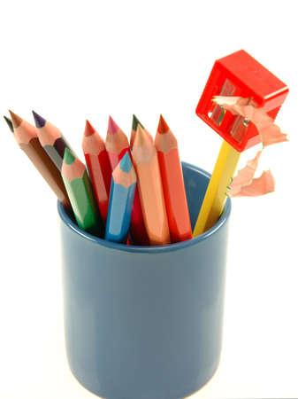 Pencils and sharpener in blue mug photo
