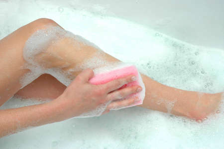woman is washing legs in the bathtub  photo