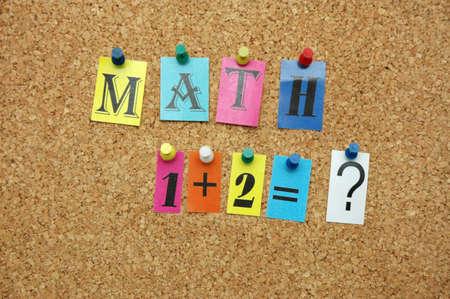 Mathematical symbols pinned on noticeboard photo