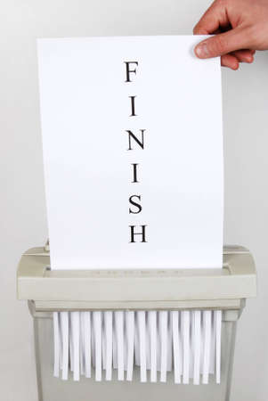 Paper shredder containing single sheet of paper with FINISH written on it photo