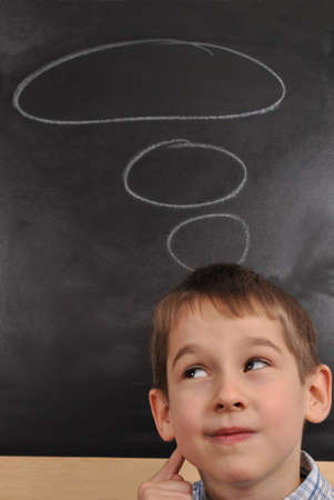 The boy is thinking by the blackboard Stock Photo - 13485162