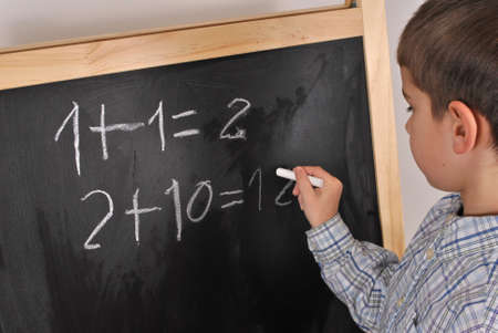 Junior pupil by the blackboard is solving mathematical problems photo