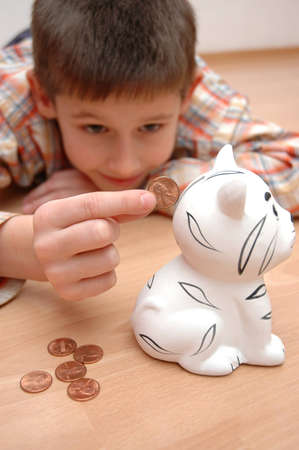 child save coins to the money box, coin bank photo