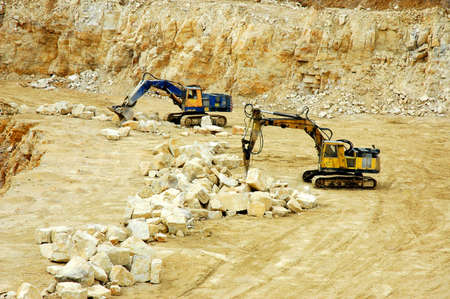 Rock crusher and digger in quarry Stock Photo