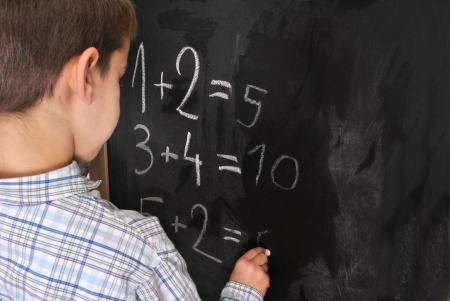 Junior pupil by the blackboard is solving mathematical problems Stock Photo