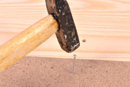 hammering: Hammering in a nail to the board Stock Photo