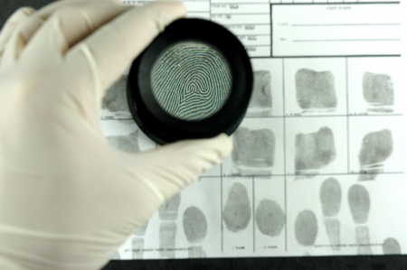 comparing the fingerprint through the dactyloscopic magnifier glass
