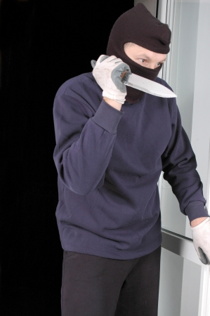 Murderer in the balaclava with the knife in the hand photo