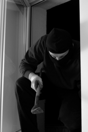 looting: The thief in the balaclava is coming in through the window home Stock Photo