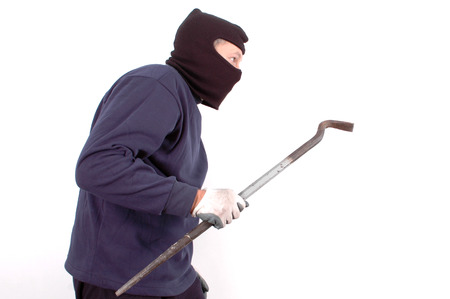 looting: Thief in the balaclava and with crowbar in the hand at home