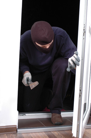 only one mid adult male: Thief in the balaclava and with crowbar in the hand at home