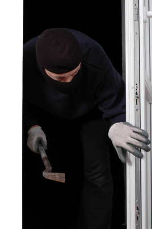 one mid adult man only: Thief in the balaclava and with crowbar in the hand at home