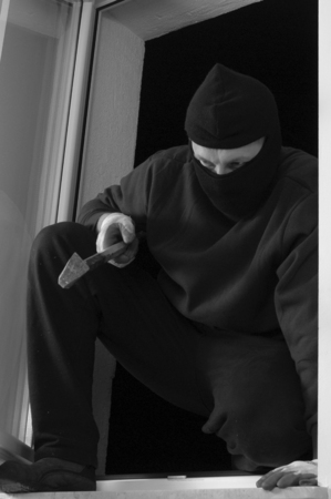 organized crime: The thief in the balaclava is coming in through the window home Stock Photo