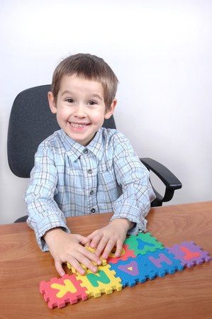 young boy makes his first word woth puzzle letters photo