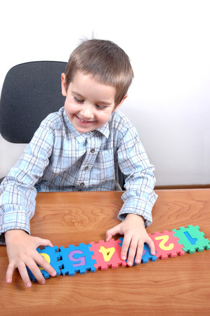 child playing with puzzle numbers photo